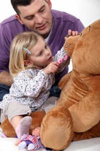 Father and daughter playing dentist with a teddy bear
